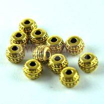 Fémgyöngy - arany színű  - 7 x 5 mm